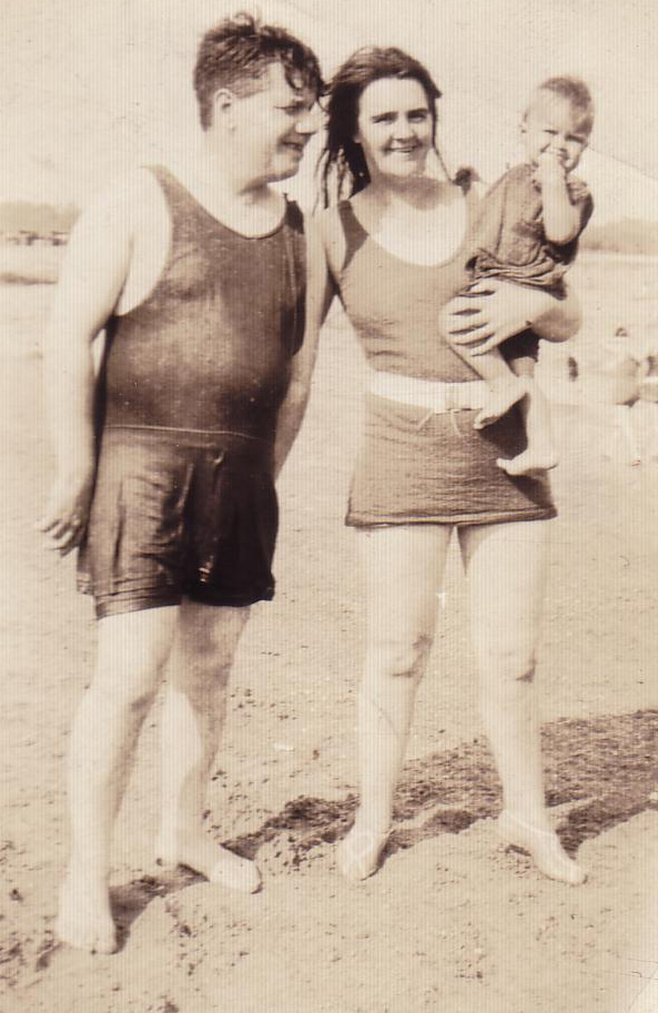 Couple In Swimsuits With Young Child On The Beach 1930s
