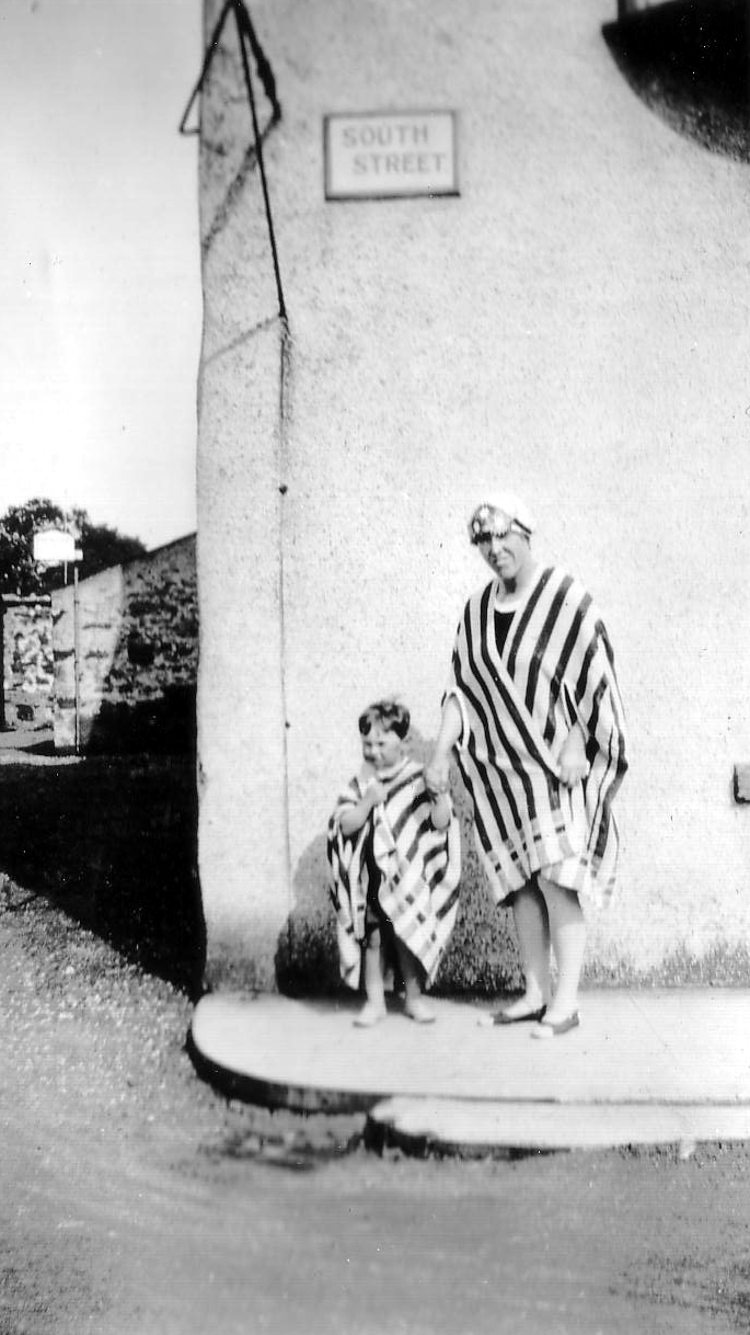 Woman And Boy Standing In Beach Towels On Corner Of Street c.1930