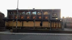 The Merlin bar closed due to coronavirus pandemic , windows boarded up